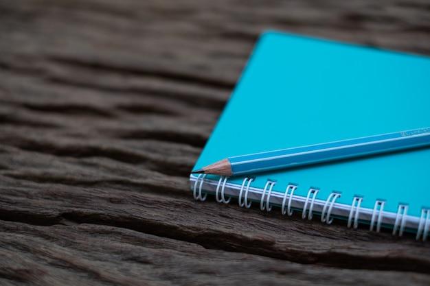 Lápis em cima da maquete do livro na velha mesa de madeira ao fundo,