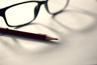 Lápis em papel com óculos