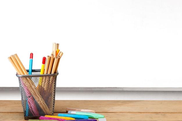 Lápis em uma cesta fixa e giz de cera com fundo de quadro branco. conceito de volta às aulas