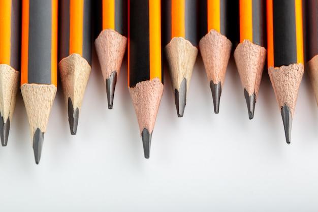 Lápis grafite alinhado projetado olhar mais atento na parede branca