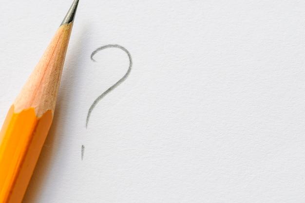 Lápis junto ao ponto de interrogação em papel branco