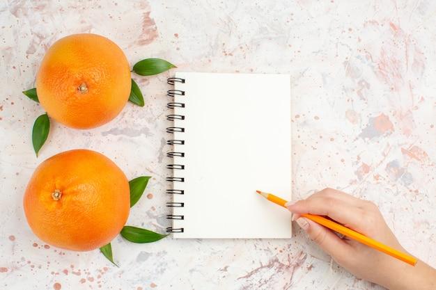 Lápis laranja de caderno de laranjas frescas de vista superior na mão feminina na superfície isolada brilhante com espaço de cópia
