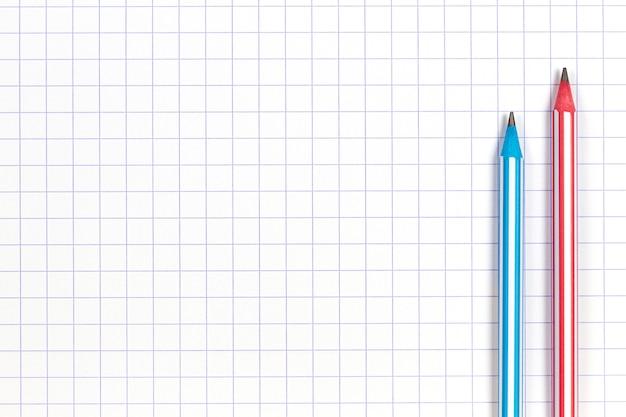 Lápis listrado no fundo do caderno de papel quadriculado branco