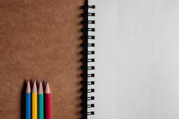 Lápis multi-coloridas com notas marrons em papel pardo