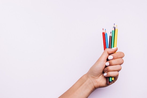 Lápis multi-coloridas em uma mão feminina com uma manicure em um fundo rosa