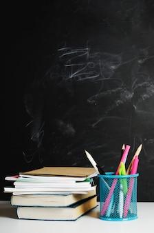 Lápis multicoloridos, canetas em um carrinho e livros com cadernos são empilhados em uma mesa branca no contexto de um quadro negro escolar pintado com giz. copie o espaço.