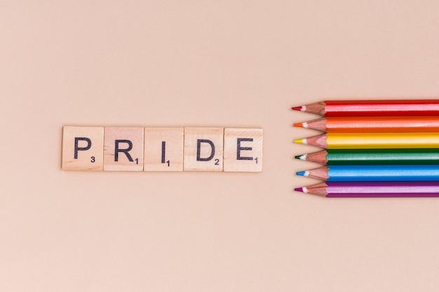Lápis multicoloridos e texto orgulho no fundo bege