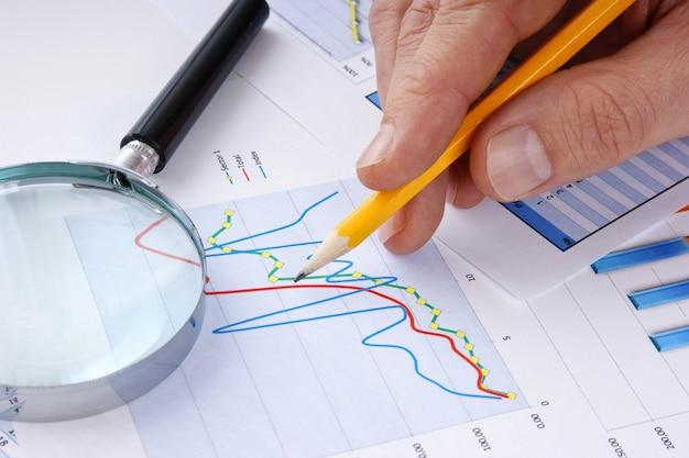 Lápis na mão e gráfico de papel de trabalho
