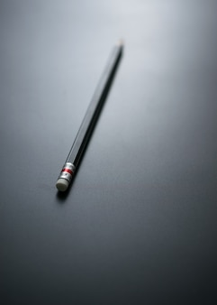Lápis no foco do quadro-negro no eliminador de lápis para o projeto do fundo do conceito do negócio do erro.