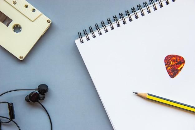 Lápis, palheta e notebook no piso cinza