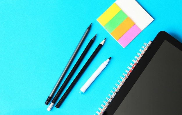 Lápis, papel de escrita e tablett em um fundo azul e de volta ao conceito da escola.