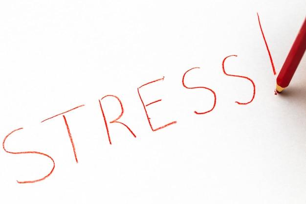 Lápis pastel vermelho para escrever a palavra - stress - sublinhado.