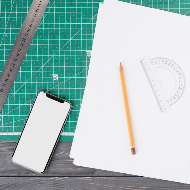 Lápis perto de folhas, smartphone, régua e transferidor