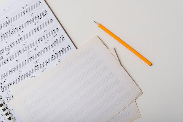 Lápis perto de partituras