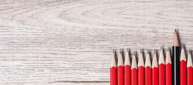 Lápis preto diferente da multidão de lápis vermelhos.