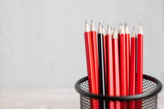 Lápis preto diferente da multidão de lápis vermelhos