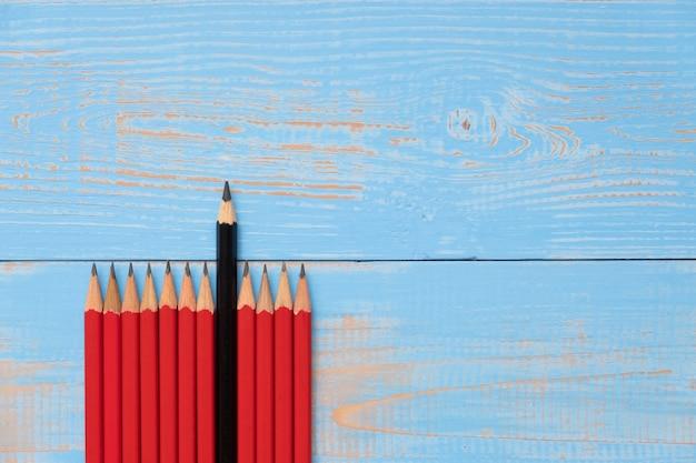 Lápis preto e lápis vermelhos no fundo de madeira azul.