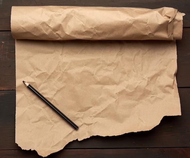 Lápis preto e rolo de papel marrom sem torção sobre uma superfície de madeira de tábuas velhas