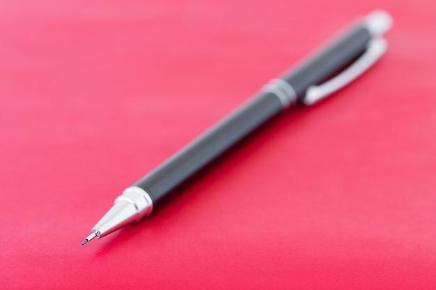 Lápis preto na superfície vermelha do caderno conceito de educação