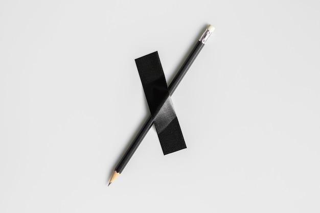Lápis preto preso com fita de pano preto.
