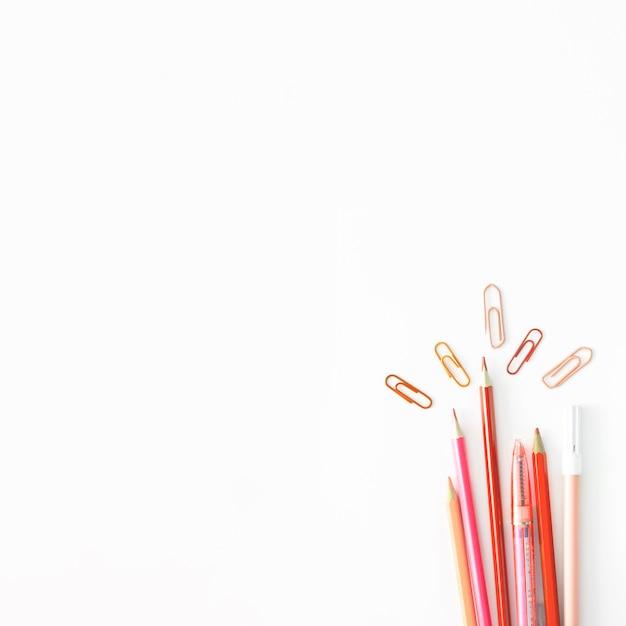 Lápis rosa e clipes na mesa branca