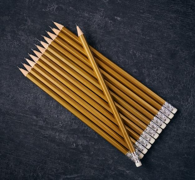 Lápis simples de cor dourada em espaço cinza
