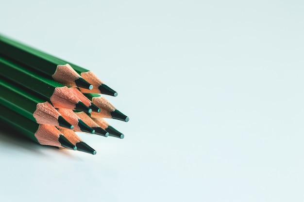 Lápis verdes sobre fundo branco. escritório, desenho.