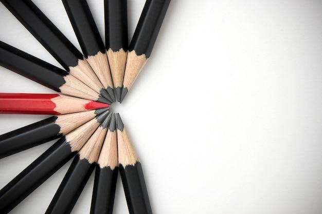 Lápis vermelho que está para fora da multidão de companheiros pretos idênticos da abundância na tabela branca.