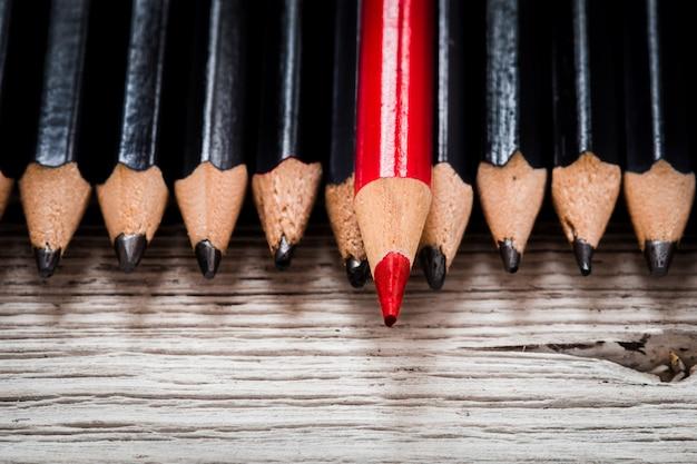 Lápis vermelho se destaca da multidão de preto sobre fundo branco de madeira.
