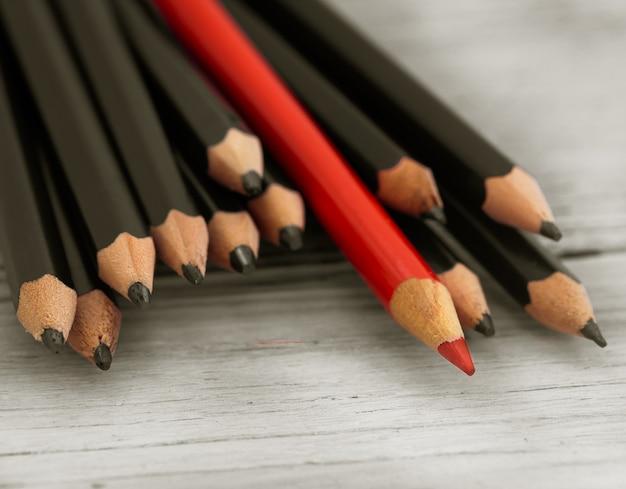 Lápis vermelho se destaca na multidão de lápis preto sobre fundo branco de madeira.