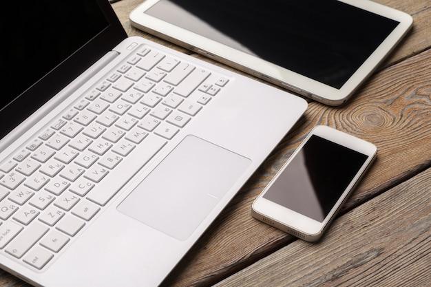 Laptop aberto com tablet digital e smartphone branco close-up vista superior