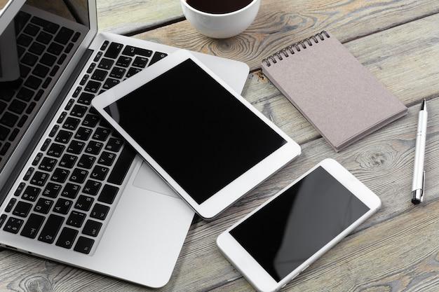 Laptop aberto com tablet digital e smartphone close-up
