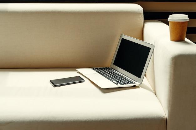 Laptop aberto na mesa perto do sofá