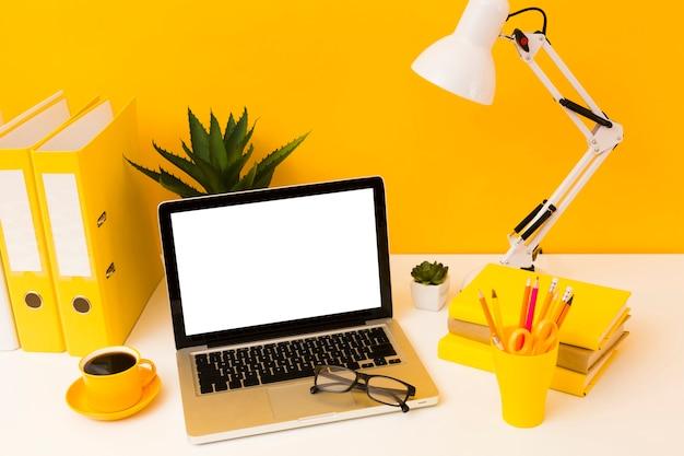 Laptop ao lado de papelaria amarelo Foto Premium