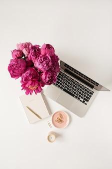 Laptop, buquê de flores de tulipa de peônia rosa linda e caderno na mesa branca. camada plana, vista superior