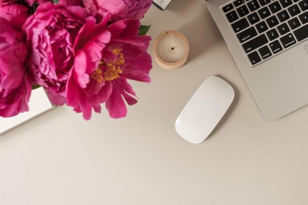 Laptop, buquê de flores de tulipa de peônia rosa linda na mesa bege. camada plana, vista superior