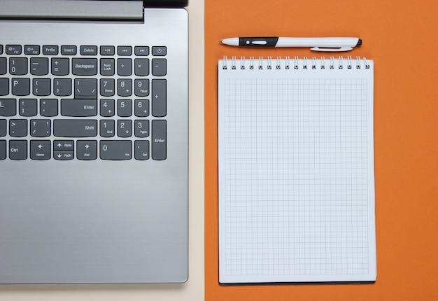 Laptop, caderno com caneta em papel pardo. foto de estúdio