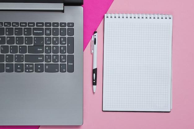 Laptop, caderno com caneta em um papel colorido