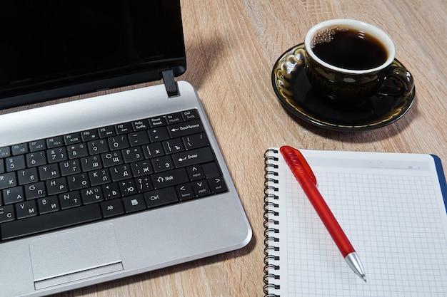 Laptop, caderno de papel com caneta e xícara de café em cima da mesa close-up