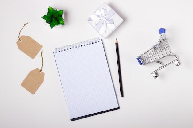 Laptop, caderno e carrinho de compras em um fundo branco