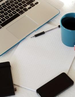 Laptop, caneca e bloco de notas