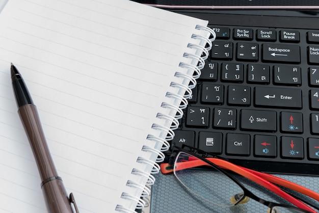 Laptop, caneta, bloco de notas e óculos