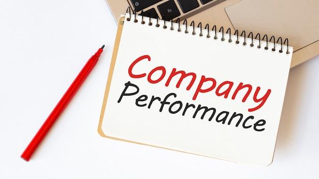 Laptop, caneta vermelha e bloco de notas com texto desempenho da empresa
