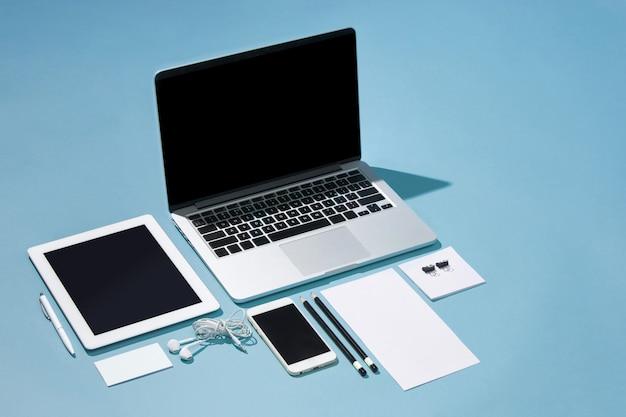 Laptop, canetas, telefone, observe com tela em branco na mesa
