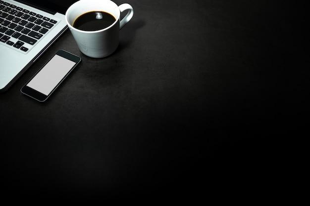 Laptop, celular com tela branca e uma xícara de café preto contra o fundo escuro vazio