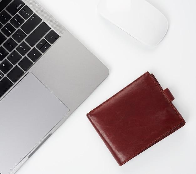 Laptop cinza aberto fica em uma mesa branca, ao lado de um mouse sem fio, local de trabalho freelancer