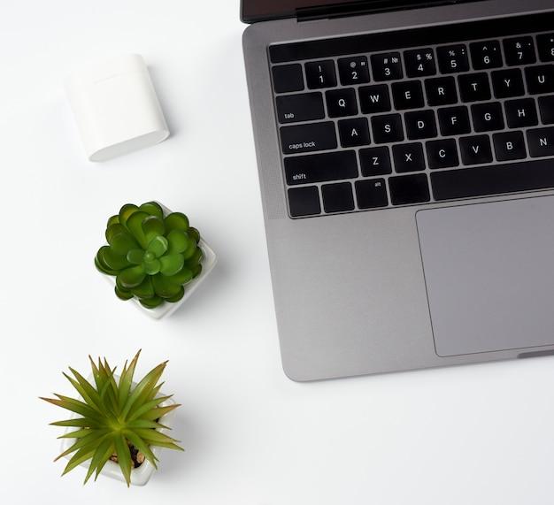 Laptop cinza aberto fica em uma mesa branca, local de trabalho freelancer