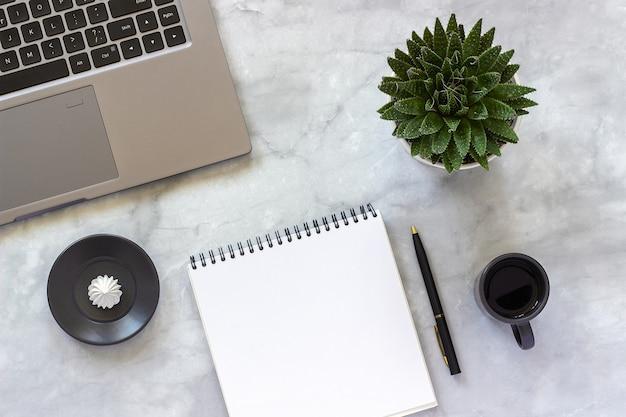Laptop cinza, abrir o bloco de notas vazio, xícara de café, suculentas em mármore