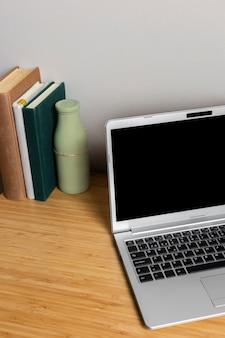 Laptop cinza com livros na mesa de madeira