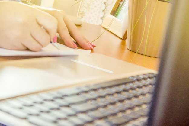 Laptop close-up de um teclado e uma xícara de café quente de manhã. foco seletivo.